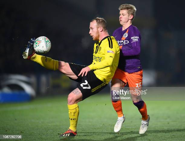 Liam Boyce of Burton Albion battles for possession with Oleksandr Zinchenko of Manchester City during the Carabao Cup Semi Final Second Leg match...