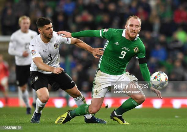 Liam Boyce of Northern Ireland and Aleksander Dragovic of Austria compete for the ball during the UEFA Nations League B group three match between...