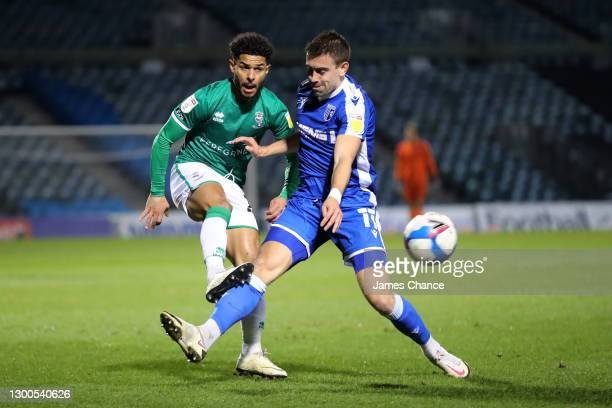 Liam Bridcutt of Lincoln City shoots under pressure from Oliver Lee of Gillingham FC during the Sky Bet League One match between Gillingham and...