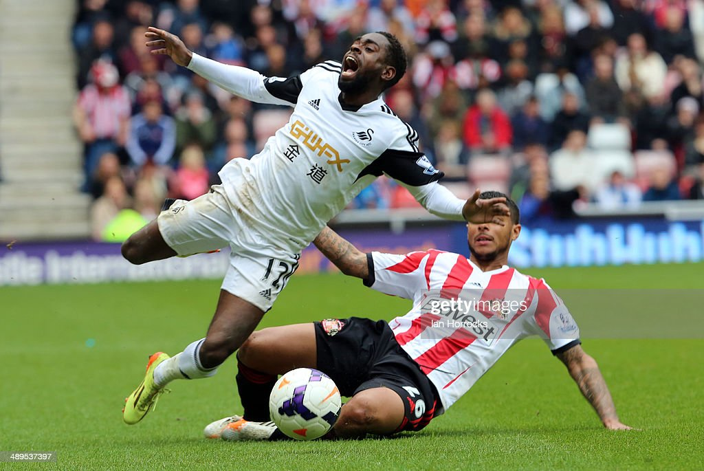 Liam Bridcutt of Sunderland (R) brings down Nathan Dyer of Swansea City during the Barclays Premier League match between Sunderland and Swansea City at The Stadium of Light on May 11, 2014 in Sunderland, England.