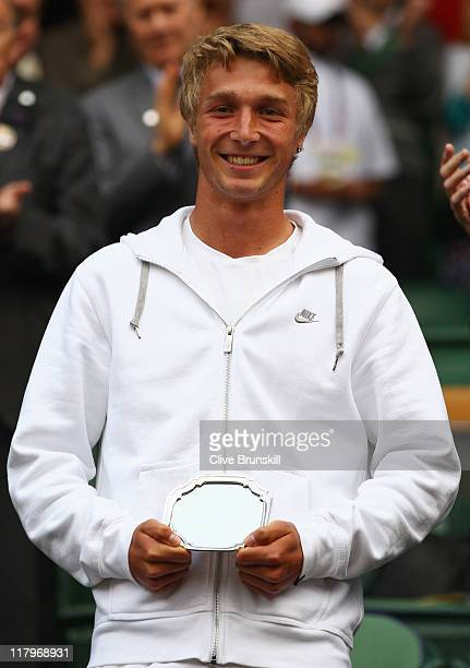 Liam Broady of Great Britain holds up his second place trophy after losing his final round boy's match against Luke Saville of Australia on Day...