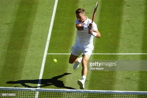 Liam Broady of Great Britain returns to Milos Raonic of Canada during their Men's Singles first round match on day one of the Wimbledon Lawn Tennis...