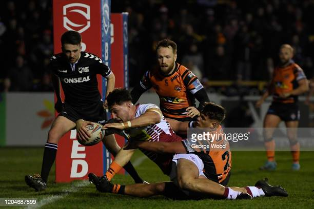 Liam Byrne of Wigan Warriors scores his side's first try whilst being under pressure by Jacques O'Neill of Castleford Tigers during the Betfred Super...