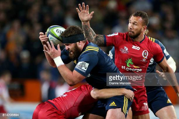 Liam Coltman of the Highlanders tries to break through the tackle of James Tuttle of the Reds during the round 17 Super Rugby match between the...