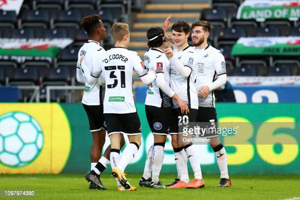 Liam Cullen of Swansea City celebrates with teammates Jamal Lowe, Oli Cooper, Yan Dhanda, and Ryan Manning after scoring his team's fourth goal...
