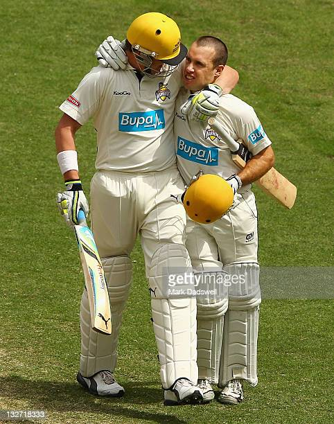 Liam Davis of the Warriors celebrates his century with Marcus North during day four of the Sheffield Shield match between the Victoria Bushrangers...