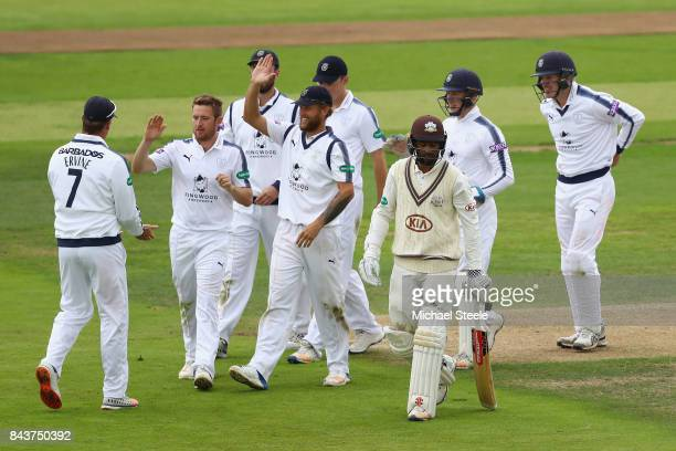 Liam Dawson of Hampshire high fives Sean Ervine after taking a catch to dismiss Ryan Patel of Surreyduring day three of the Specsavers County...