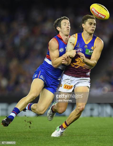Liam Dawson of the Lions handballs whilst being tackled by Robert Murphy of the Bulldogs during the round five AFL match between the Western Bulldogs...