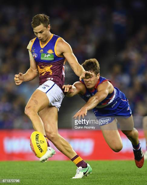 Liam Dawson of the Lions kicks whilst being tackled by Josh Dunkley of the Bulldogs during the round five AFL match between the Western Bulldogs and...