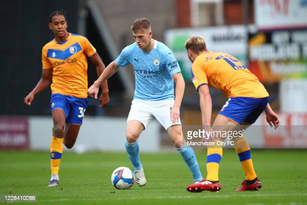 Liam Delap of Manchester City in action with Aaron O'Driscoll and Alistair Smith of Mansfield Town during the EFL Trophy match between Mansfield Town...