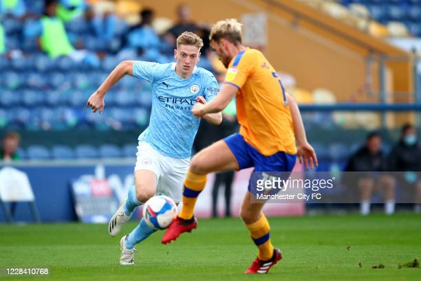Liam Delap of Manchester City in action with Aaron O'Driscoll of Mansfield Town during the EFL Trophy match between Mansfield Town and Manchester...