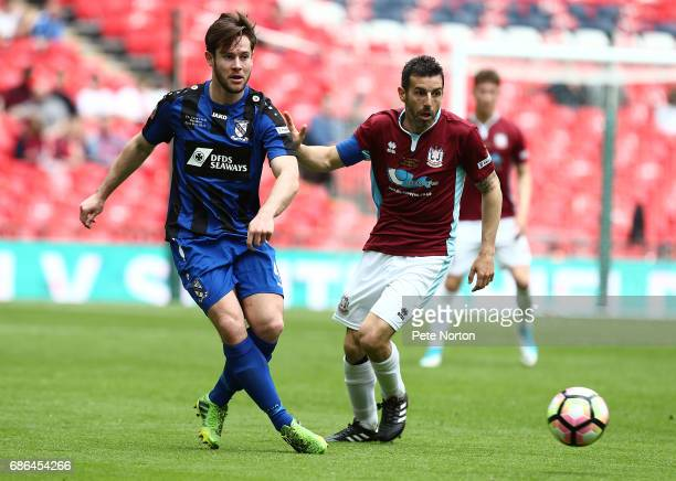 Liam Dickens of Cleethorpes Town plays the ball watched by Julio Arca of South Shields during The Buildbase FA Vase Final between South Shields and...