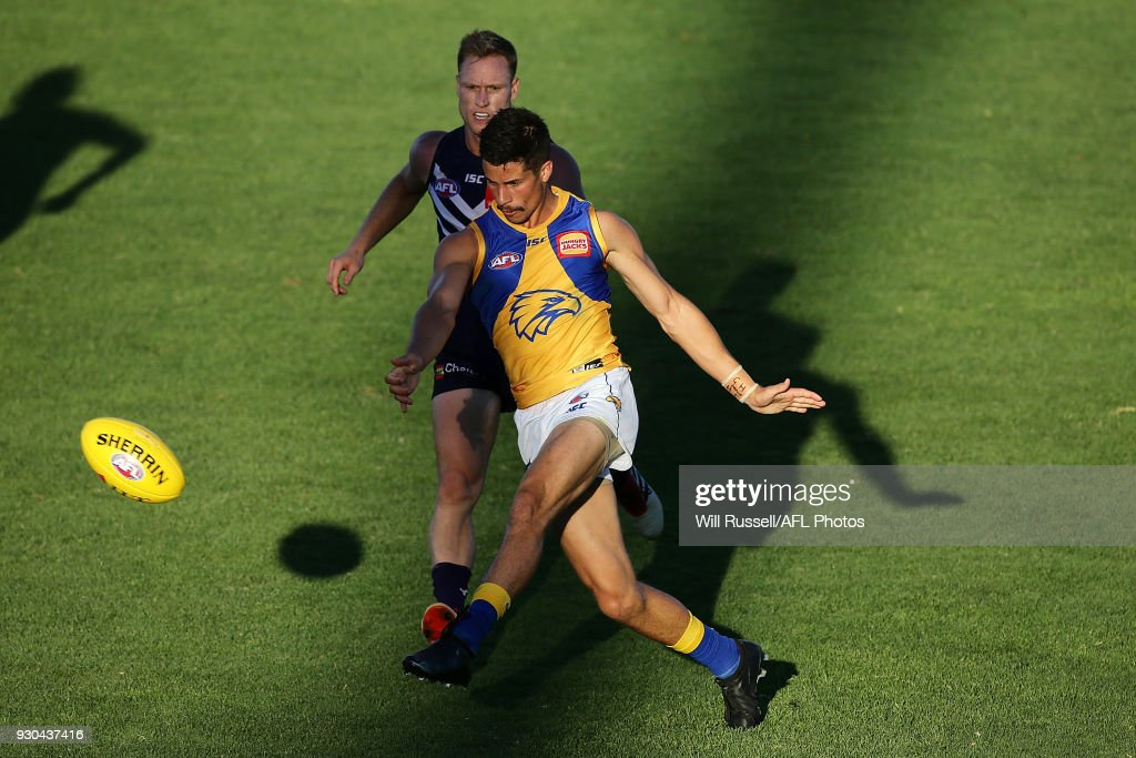 Liam Duggan of the Eagles kicks the ball under pressure from Brandon Matera of the Dockers during the JLT Community Series AFL match between the Fremantle Dockers and the West Coast Eagles at HBF Arena on March 11, 2018 in Perth, Australia.