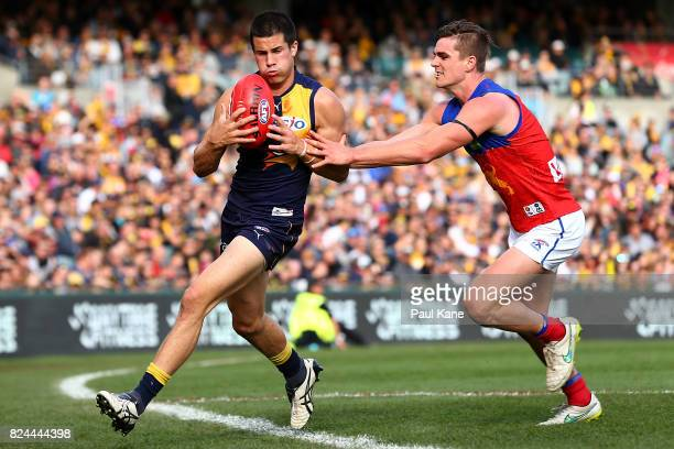 Liam Duggan of the Eagles takes the ball over the boundary line against Ben Keays of the Lions during the round 19 AFL match between the West Coast...