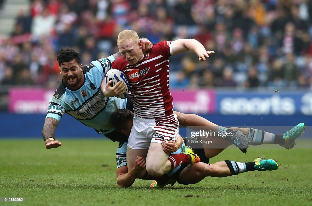 Liam Farrell of Wigan Warriors is tackled by Andrew Fifita of Cronulla-Sutherland Sharks during the Dacia World Club Challenge match between Wigan Warriors and Cronulla-Sutherland Sharks at DW Stadium on February 19, 2017 in Wigan, England.