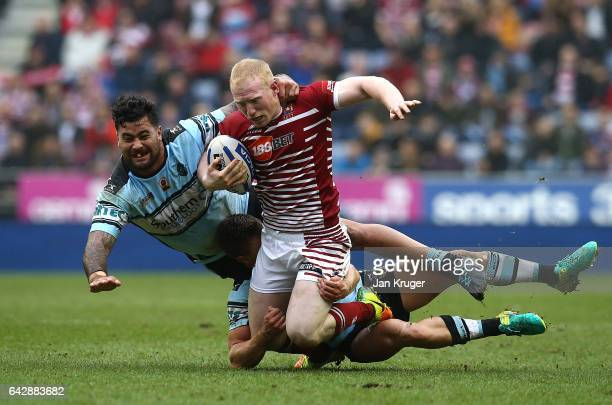 Liam Farrell of Wigan Warriors is tackled by Andrew Fifita of CronullaSutherland Sharks during the Dacia World Club Challenge match between Wigan...