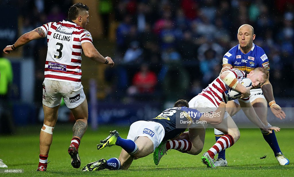 Liam Farrell of Wigan Warriors is taken down by Kevin Sinfield (c) of Leeds Rhinos in a tackle during the Round 2 match of the First Utility Super League Super 8s between Leeds Rhinos and Wigan Warriors at Headingley Carnegie Stadium on August 14, 2015 in Leeds, England.