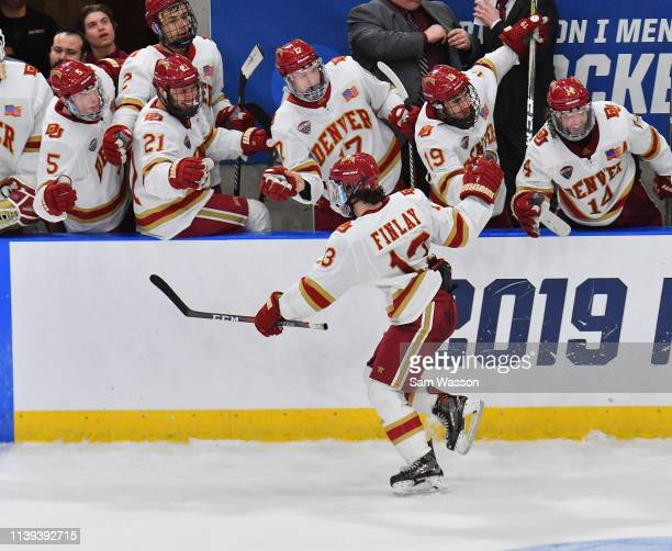 Liam Finlay of the Denver Pioneers celebrates with the bench after scoring a goal against the American International Yellow Jackets in the third...