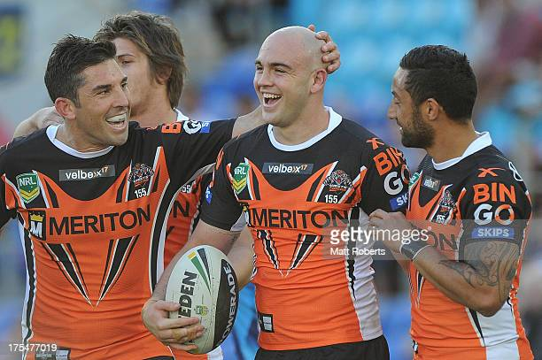 Liam Fulton of the Tigers celebrates a try with Braith Anasta and Benji Marshall during the round 21 NRL match between the Gold Coast Titans and the...