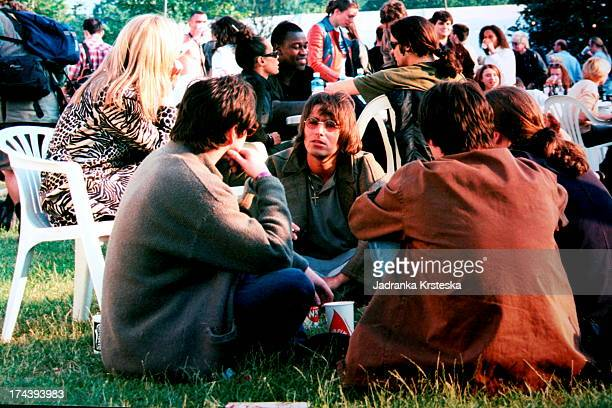 Liam Gallagher of Oasis sits on the grass with a group of people including Patsy Kensit before the Sex Pistols' reunion gig at Finsbury Park London...