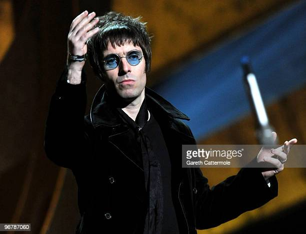 Liam Gallagher throws his microphone into the audience after accepting Oasis' award for 'Best Album of 30 Years' on stage at The Brit Awards 2010 at...