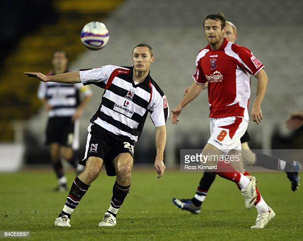 Liam Hatch of Darlington is challenged by Peter Holmes of Rotherham during the Johnstone's Paint Trophy northern area semifinal match between...
