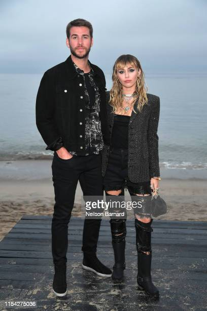 Liam Hemsworth and Miley Cyrus attend the Saint Laurent Mens Spring Summer 20 Show on June 06 2019 in Paradise Cove Malibu California