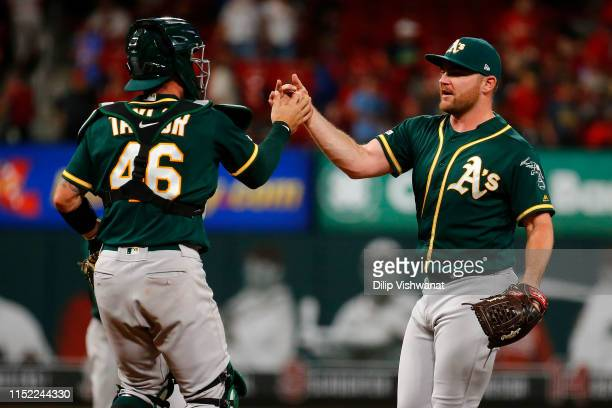Liam Hendriks and Beau Taylor of the Oakland Athletics celebrate after beating the St Louis Cardinals at Busch Stadium on June 26 2019 in St Louis...