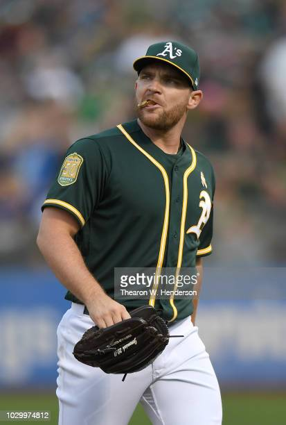 Liam Hendriks of the Oakland Athletics looks on as he walks back to the dugout after he was taken out of the game against the Seattle Mariners in the...