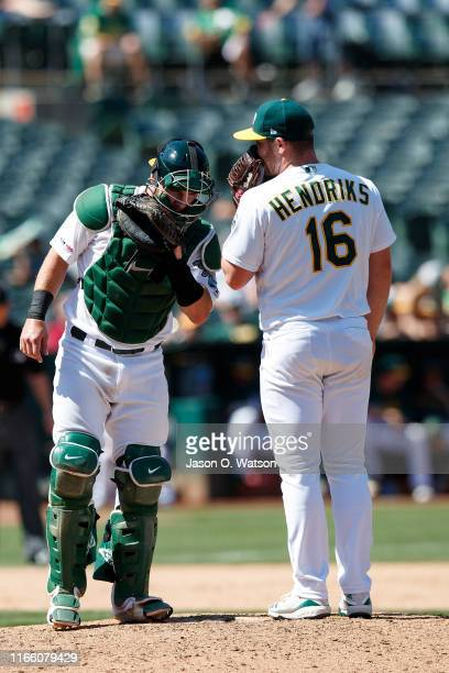 Liam Hendriks of the Oakland Athletics talks to Chris Herrmann on the pitchers mound during the eighth inning against the Texas Rangers at the...