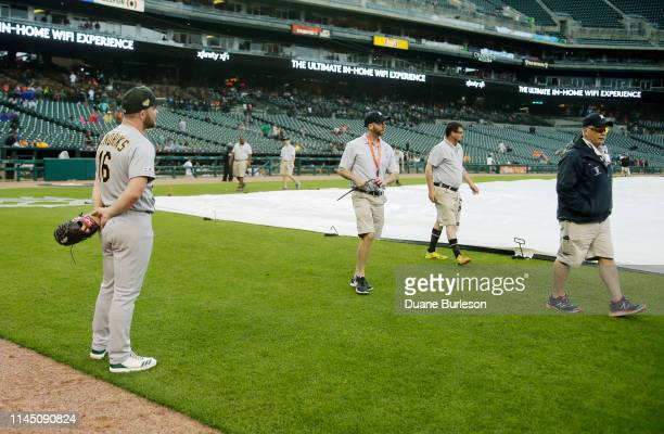 Liam Hendriks of the Oakland Athletics watches the grounds crew walk away after coving the field at Comerica Park during the seventh inning of a game...