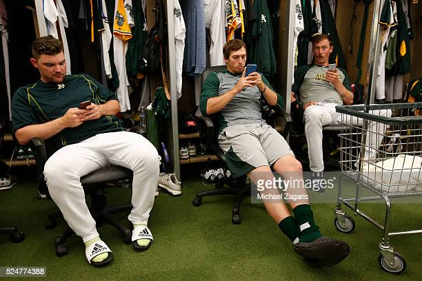 Liam Hendriks Ryan Dull and John Axford of the Oakland Athletics check their phones in the clubhouse prior to the game against the Los Angeles Angels...