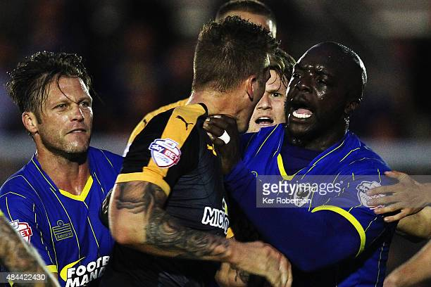 Liam Hughes of Cambridge United confronts Adebayo Akinfenwa of AFC Wimbledon as tempers flare during the Sky Bet League Two match between AFC...