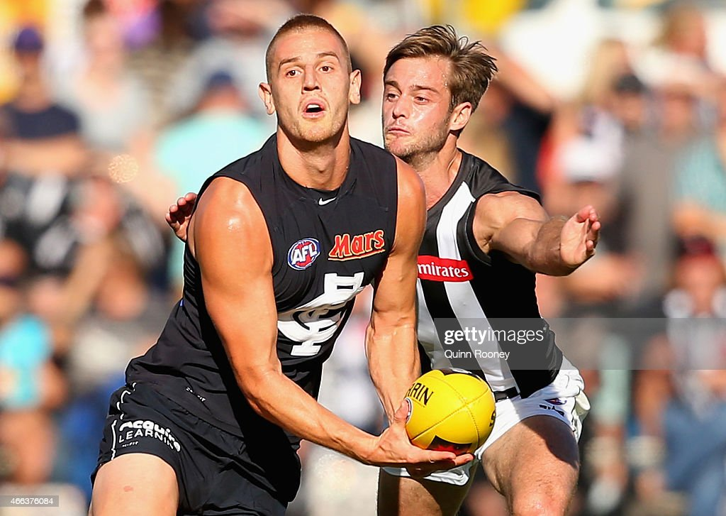 Liam Jones of the Blues handballs whilst being tackled by Alan Toovey of the Magpies during the NAB Challenge AFL match between the Collingwood Magpies and the Carlton Blues at Queen Elizabeth Oval on March 15, 2015 in Bendigo, Australia.