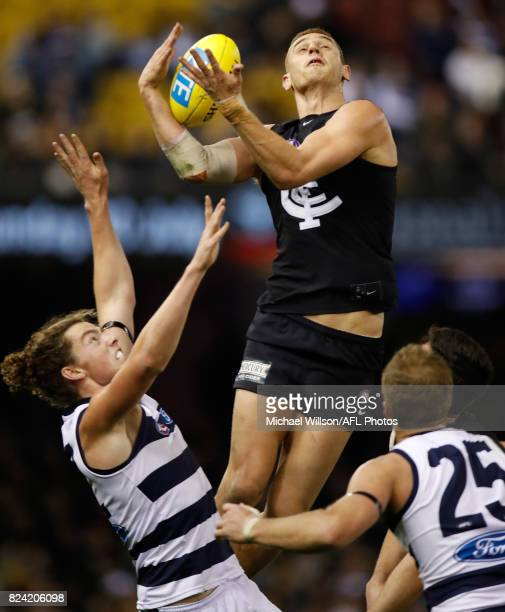 Liam Jones of the Blues marks over Wylie Buzza of the Cats during the 2017 AFL round 19 match between the Carlton Blues and the Geelong Cats at...