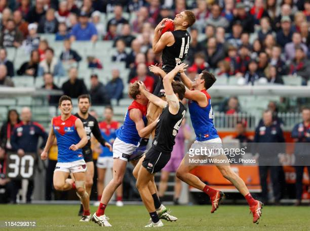 Liam Jones of the Blues takes a high mark over Mitch Hannan of the Demons during the 2019 AFL round 16 match between the Carlton Blues and the...