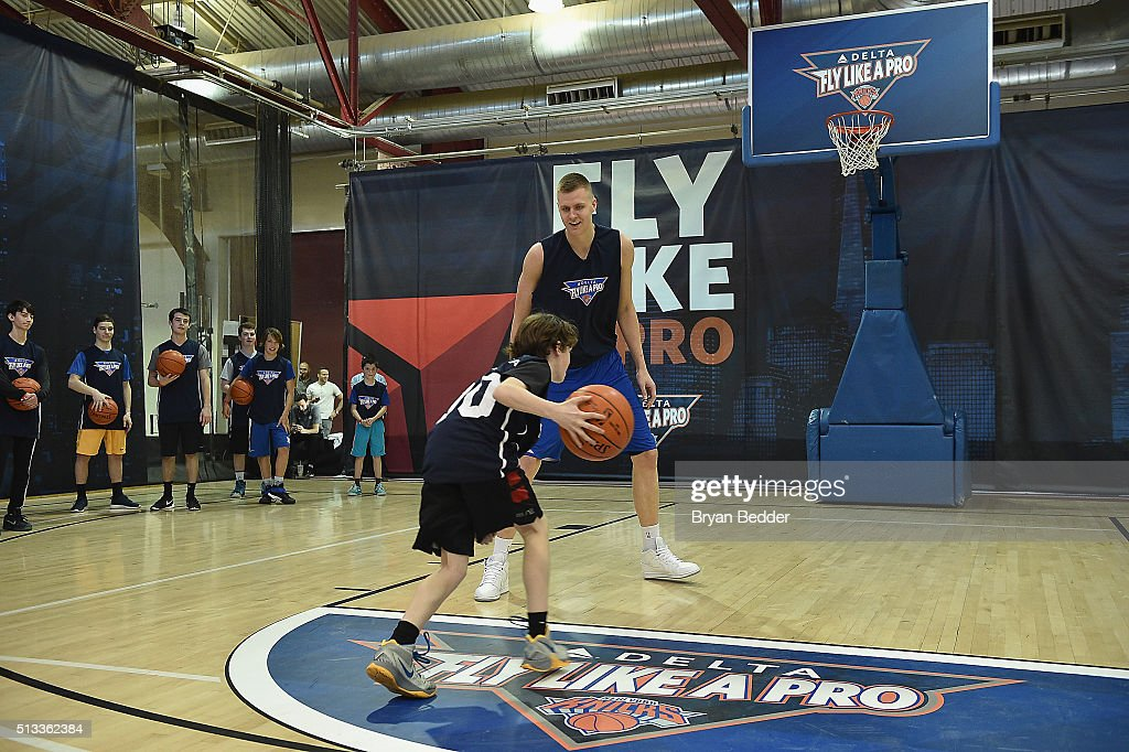 Liam Kennelly (L) and NBA basketball player for the New York Knicks, Kristaps Porzingis celebrate Delta Air Lines Fly Like a Pro campaign with a H-O-R-S-E competition at Chelsea Piers in New York City on March 2, 2016.