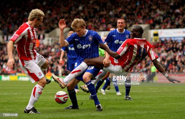 Liam Lawrence and Mamady Sidibe of Stoke get tangled up with Dan Harding of Ipswich during the Coca-Cola Championship match between Stoke City and...