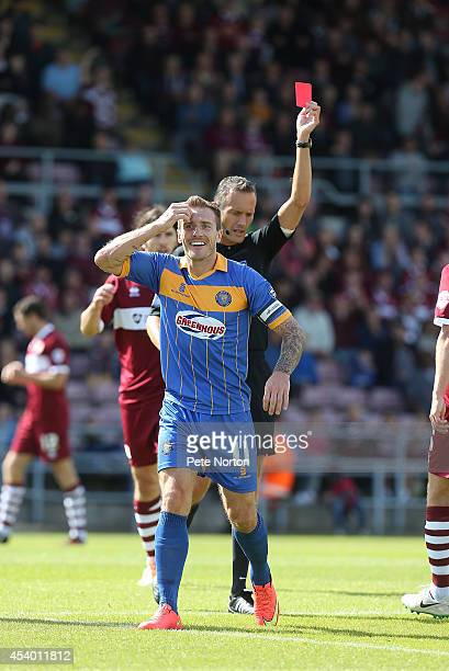 Liam Lawrence of Shrewsbury Town is shown a red card by referee Darren Deadman during the Sky Bet League Two match between Northampton Town and...