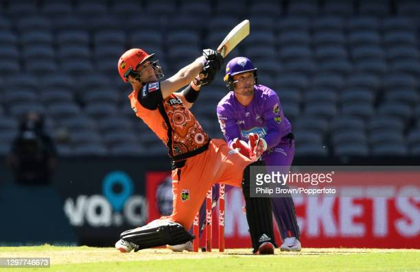 Liam Livingstone of Scorchers hits a six as Ben MCDermott watches during the Big Bash League match between the Hobart Hurricanes and the Perth...