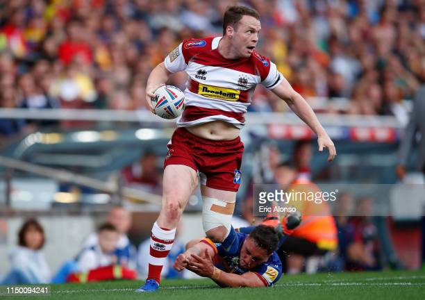 Liam Marshall of Wigan Warriors runs to score past Tony Gigot of Catalans Dragons during the Betfred Super League match at Camp Nou on May 18, 2019...