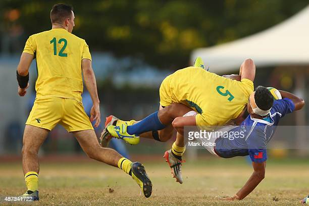 Liam McNamara of Australia watches on as Simon Kenewell of Australia tackles Mathew Taula of Samoa during the boys match between Australia and Samoa...