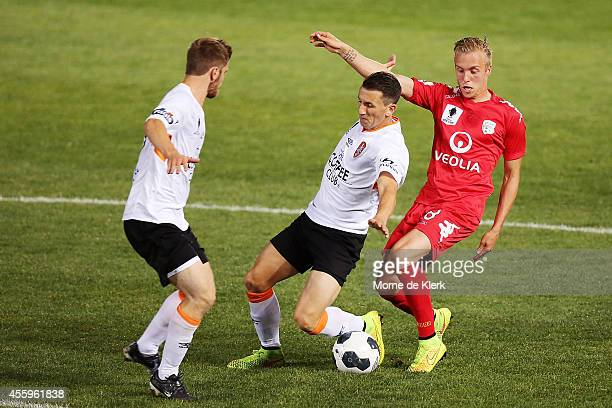Liam Miller of Brisbane is tackled by James Jeggo of Adelaide during the FFA Cup match between Adelaide United and Brisbane Roar at the Coopers...