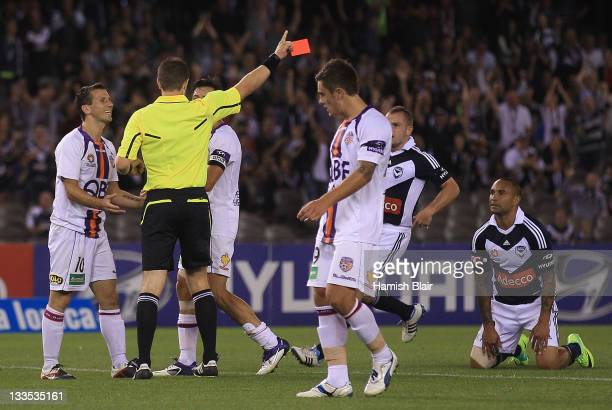 Liam Miller of the GLory is shown a red card by referee Chris Beath for a challenge on Archie Thompson of the Victory during the round seven ALeague...