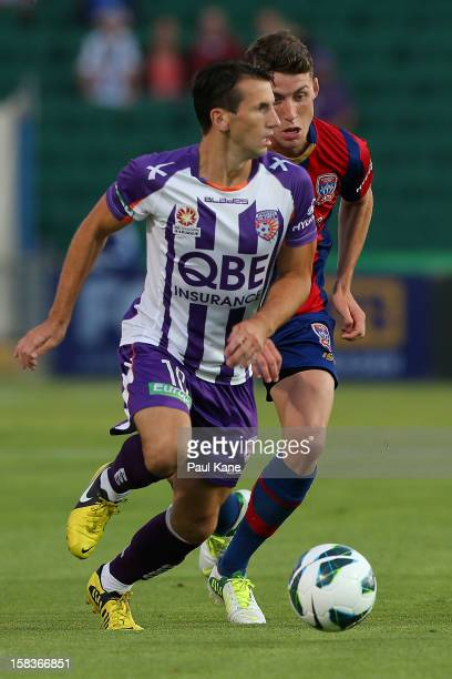 Liam Miller of the Glory looks to pass the ball against Scott Neville of the Jets during the round 11 ALeague match between the Perth Glory and the...