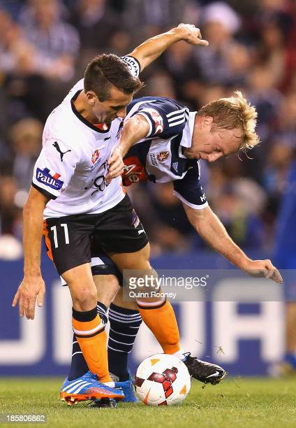 Liam Miller of the Roar and Mitchell Nichols of the Victory compete for the ball during the round three ALeague match between Melbourne Victory and...