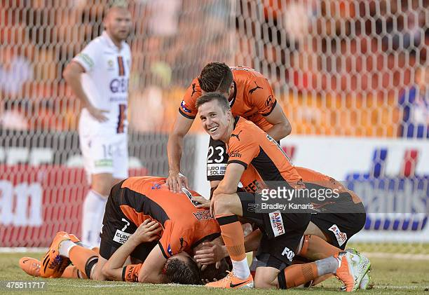 Liam Miller of the Roar is jumped on by his team mates as they celebrate victory during the round 21 ALeague match between Brisbane Roar and Perth...