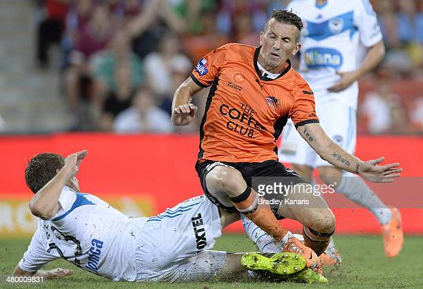 Liam Miller of the Roar is tackled by Adrian Leijer of the Victory during the round 24 ALeague match between Brisbane Roar and Melbourne Victory at...