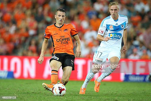 Liam Miller of the Roar kicks the ball past James Jeggo of the Victory during the round 24 ALeague match between Brisbane Roar and Melbourne Victory...