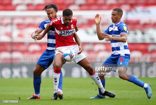 Liam Moore and Andy Rinomhota of Reading battle for possession with Chuba Akpom of Middlesbrough during the Sky Bet Championship match between...